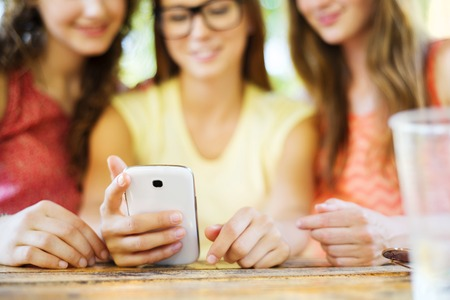 non alcoholic beverage: Three beautiful girls drinking and having fun with smartphone in pub garden Stock Photo