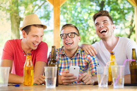 Three happy friends drinking and having fun with smartphone in pub garden photo