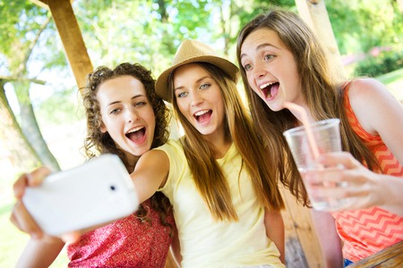 Three beautiful girls drinking and taking selfie with smartphone in pub garden photo