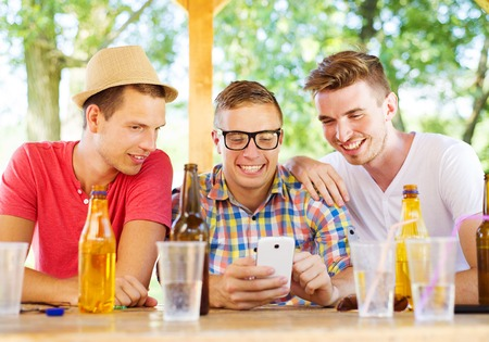 non alcoholic beer: Three happy friends drinking and having fun with smartphone in pub garden Stock Photo