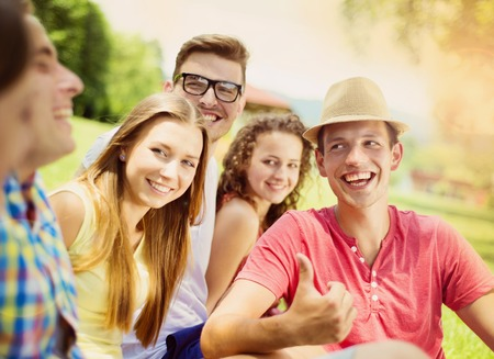 Groep jonge mensen die plezier in het park, zittend op het gras