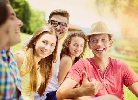 personas abrazadas: Grupo de j�venes que se divierten en el parque, sentado en la hierba Foto de archivo