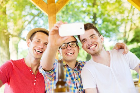 non alcoholic beverage: Three happy friends drinking and taking selfie with smartphone in pub garden