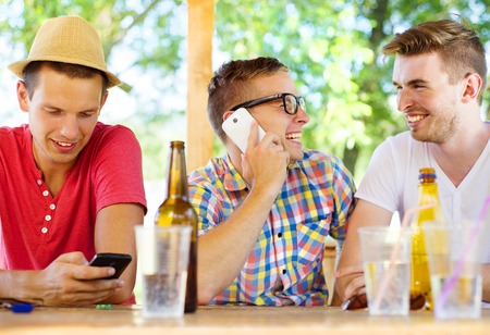 non alcoholic beer: Three happy friends drinking and having fun in pub garden Stock Photo