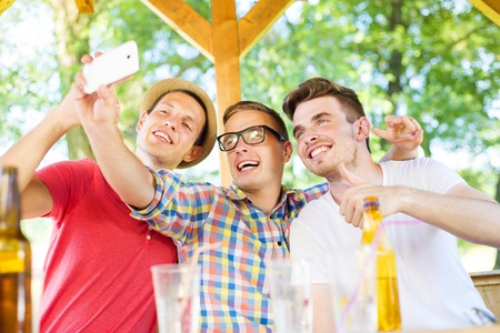 non alcoholic beer: Three happy friends drinking and taking selfie with smartphone in pub garden