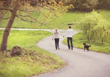 parejas caminando: Hermosa pareja tomando un paseo en el parque verde