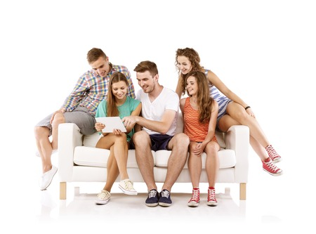 Group of happy young people sitting on sofa and using digital tablet, isolated on white background  Best friends photo