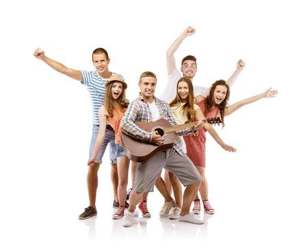 白い背景の親友に分離されたギターを楽しんで幸せな若い人たちのグループ