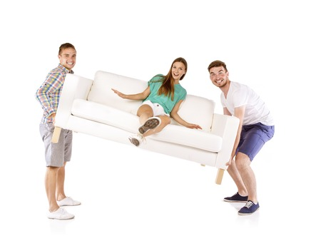 Two young handsome men lifting sofa with young beautiful woman sitting on it, isolated on white background Stockfoto