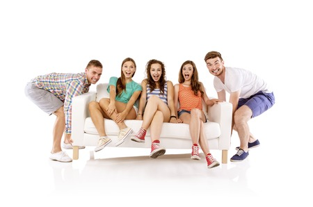 Two young handsome men lifting sofa with young beautiful women sitting on it, isolated on white background photo