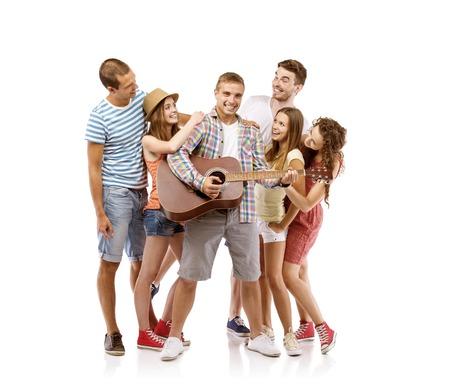 Groep gelukkige jonge mensen die plezier met gitaar, geïsoleerd op witte achtergrond Beste vrienden Stockfoto