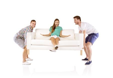 levantar peso: Dos hombres guapos j�venes sof� con una mujer hermosa joven sentado en �l, aislados en fondo blanco de elevaci�n