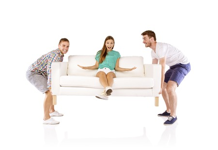 Two young handsome men lifting sofa with young beautiful woman sitting on it, isolated on white background photo