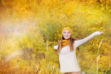 fall beauty: Portrait of beautiful girl with scarf and hat in yellow autumn nature