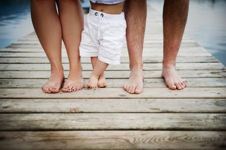 桟橋の上を歩いての小さな男の子を持つ家族のフィートのクローズ アップ