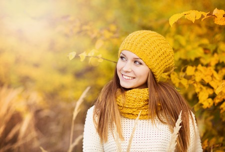 Portrait of beautiful girl with scarf and hat in yellow autumn nature photo