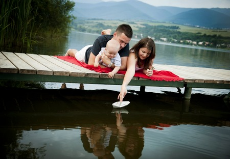 Mother and father with baby boy sitting on pier and playing with paper boat photo
