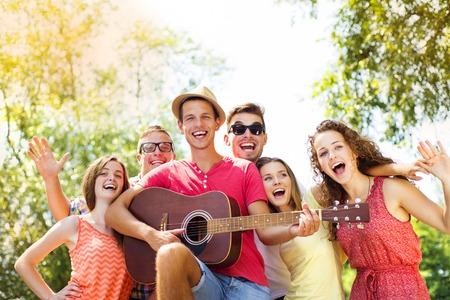 Group of happy friends with guitar having fun outdoor Standard-Bild