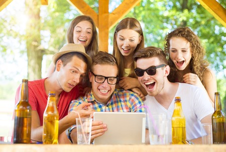 non alcoholic beer: Group of happy friends drinking and having fun with tablet in pub garden