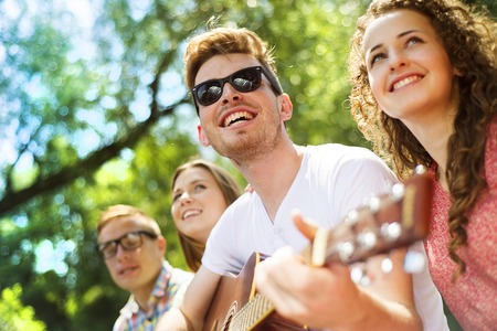 Group of happy friends with guitar having fun outdoor photo