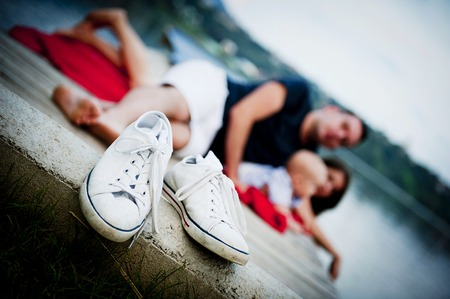 Canvas shoes detail, family with baby boy sitting on pier on the background photo