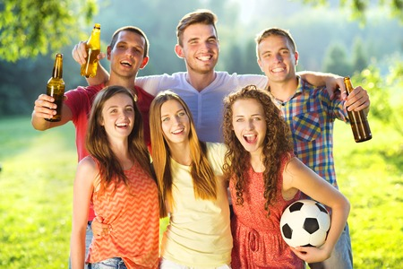 women playing soccer: Group of happy friends spending free time together in park and drinking beer Stock Photo
