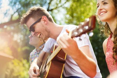 juventud: Grupo de amigos felices con la guitarra divierten al aire libre Foto de archivo