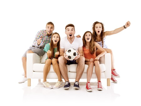 Group of happy young people sitting on sofa and holding soccer ball, isolated on white background. Best friends