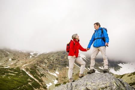 Anziano, donna, coppia di turisti escursioni a piedi, l'uomo sta contribuendo a raggiungere la roccia