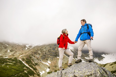 ancianos caminando: Mujer Senior pareja de turistas de excursión, el hombre está ayudando a llegar a la roca Foto de archivo