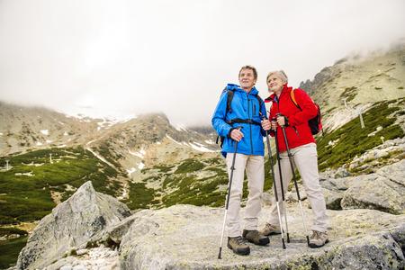 美しい山々 でハイキング シニア観光カップル