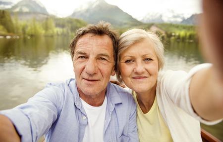 Hoger paar op boot met bergen op de achtergrond nemen selfie
