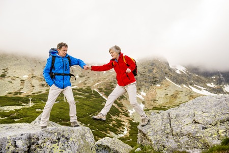 Senior tourist couple hiking, man is helping woman to get to the rock photo