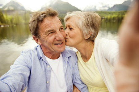 Senior couple on boat with mountains in background taking selfie photo