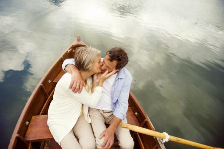 Senior couple kissing on boat on mountain tarn photo
