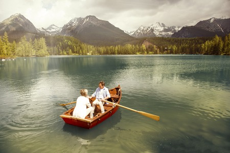 Senior couple paddling on boat on mountain tarn