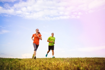 couple exercising: Cross-country trail running people at sunset. Runner couple exercising outside as part of healthy lifestyle. Stock Photo