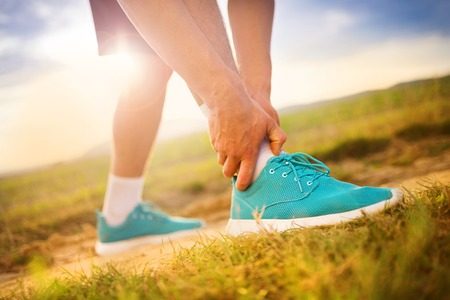 sore muscles: Runner leg and muscle pain during running training outdoors in summer nature