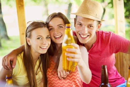 Group of happy friends drinking and having fun in pub garden photo