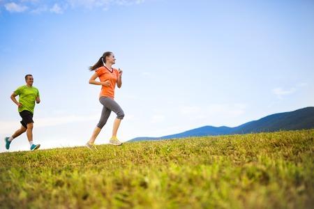 pareja saludable: Campo través del rastro corriendo a la gente al atardecer. Pareja Runner ejercicio al aire libre como parte del estilo de vida saludable. Foto de archivo