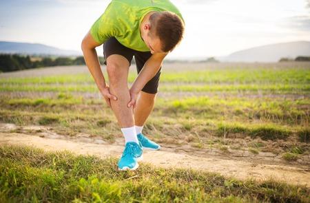 dolor muscular: Runner pierna y dolores musculares durante la carrera de entrenamiento al aire libre en la naturaleza de verano Foto de archivo
