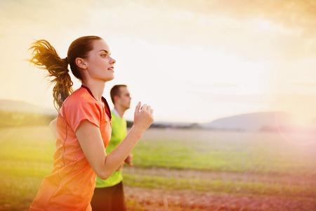 Campo través del rastro corriendo a la gente al atardecer. Pareja Runner ejercicio al aire libre como parte del estilo de vida saludable.