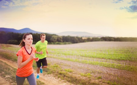outside of the country: Cross-country trail running people at sunset. Runner couple exercising outside as part of healthy lifestyle. Stock Photo