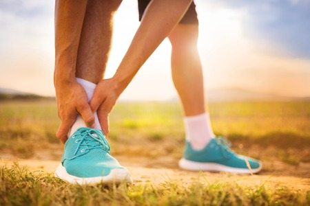 sore joints: Runner leg and muscle pain during running training outdoors in summer nature