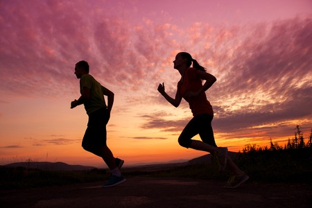 Silhouette of young couple running in sunset photo