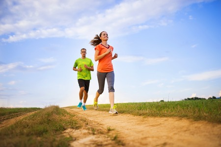 crosscountry: Cross-country trail running people at sunset. Runner couple exercising outside as part of healthy lifestyle. Stock Photo