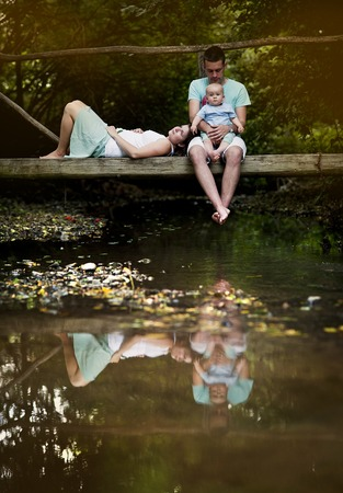Happy family with little baby boy is sitting on the bridge over the river photo