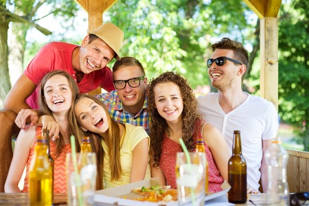 non alcoholic beer: Group of happy friends drinking and having fun in pub garden