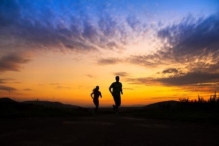 Silhouet van jonge paar lopen in zonsondergang