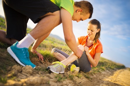 Injury - sports woman with injured knee getting help from man touching her knee. Stock Photo